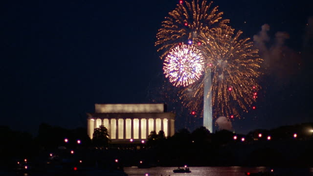 Wide shot fireworks exploding over Washington Monument and Lincoln Memorial at night / Washington, DC