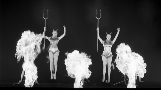 vídeos de stock e filmes b-roll de b/w 1945 wide shot five devil women holding pitchforks jumping up and down with flames in foreground - inferno fogo