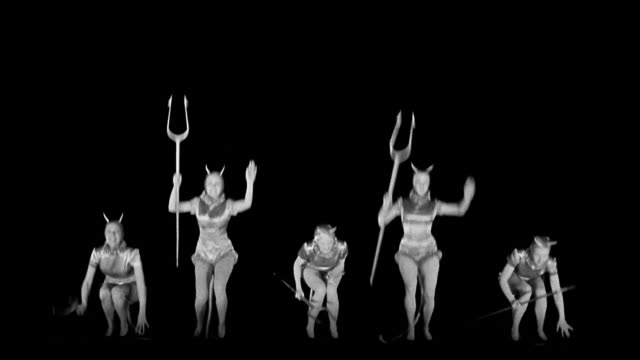 b/w 1945 wide shot five devil women holding pitchforks jumping up and down - di archivio video stock e b–roll