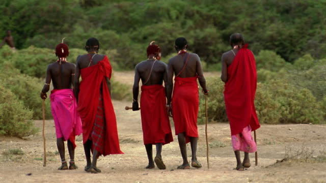 wide shot five Masai tribesmen walking on plain away from camera / Kenya