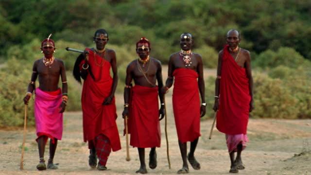 wide shot five masai tribesmen walking on plain towards camera / kenya - masai stock videos and b-roll footage