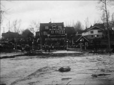 wide shot flooded street / houses + people in background / reno, nevada / newsreel - anno 1927 video stock e b–roll