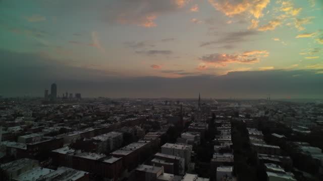 Wide shot flying over Brooklyn toward sunrise