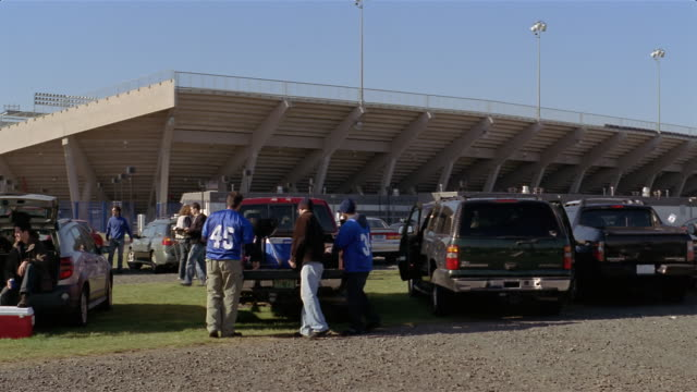 wide shot football fans arriving and unloading for tailgate party outside stadium/ connecticut - cool box stock videos and b-roll footage