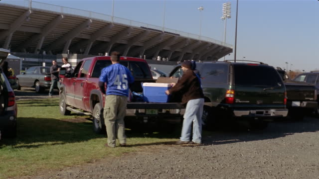 wide shot football fans unloading for tailgate party outside stadium/ connecticut - cool box stock videos & royalty-free footage