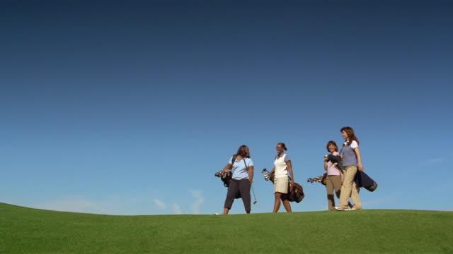 vídeos de stock, filmes e b-roll de wide shot four women golfers carrying clubs and walking - bolsa de golfe