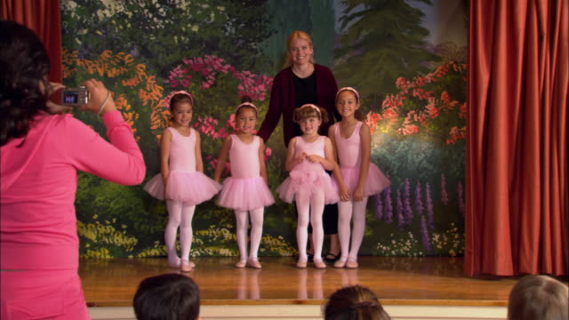 Wide shot four young girls in tutus smiling on stage with teacher / girls curtsying and losing balance / woman taking photos from audience