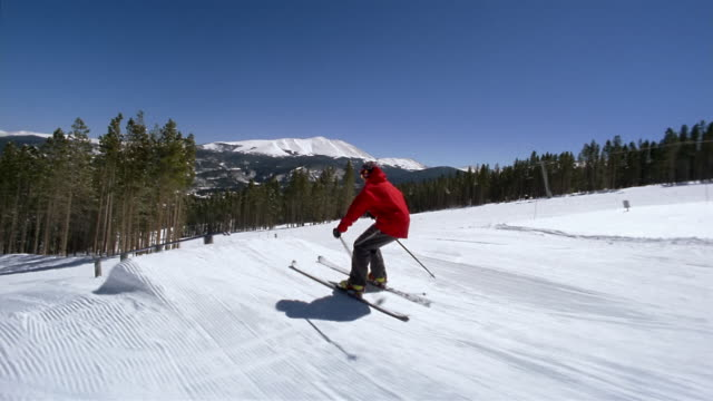 Wide shot freestyle skier jumping onto rail / sliding on rail / jumping off rail / doing lunges