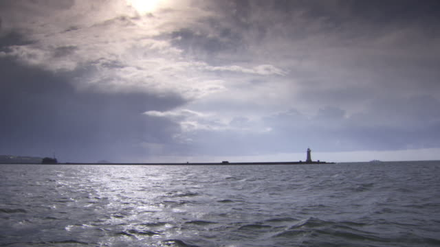 wide pov shot from a boat showing atmospheric cloud formations over a lighthouse on a peninsula jutting the waters of england's south coast, uk. - english channel stock videos and b-roll footage