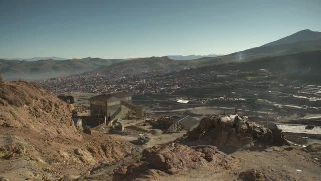wide shot from a hill showing buildings used for mining, the city of potosi and the surrounding landscape, bolivia. - bolivien stock-videos und b-roll-filmmaterial