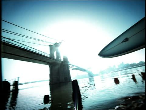 vídeos de stock, filmes e b-roll de blue high contrast wide shot pan from man holding surfboard on bank of east river to brooklyn bridge / nyc - superexposto