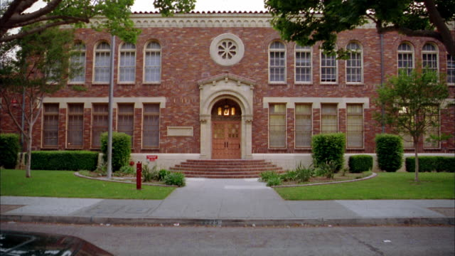wide shot front exterior of brick school building w/traffic passing in foreground - brick stock videos & royalty-free footage