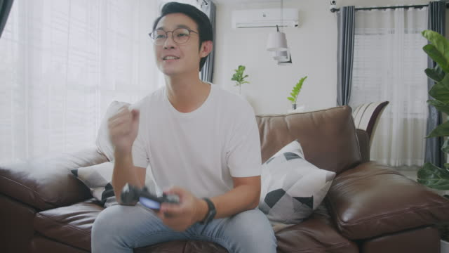 wide shot front view 4k resolution attractive adult asian man  holding joystick or game controller and playing video games console at home. man reaction enjoy his winning on his gaming. - computer game control stock videos & royalty-free footage