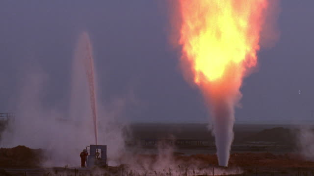 wide shot gas fire burning with workers standing by water sprayer / bakersfield, california - pipeline stock-videos und b-roll-filmmaterial