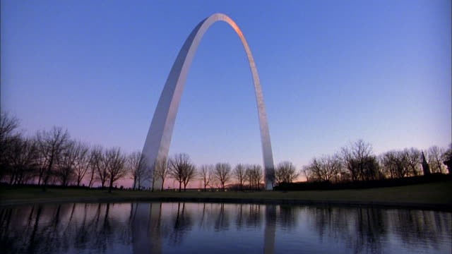 vídeos de stock e filmes b-roll de wide shot gateway arch and bare trees w/blue sky in background / st. louis - arco gateway
