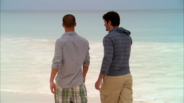 wide shot gay couple walking on beach/ harbor island, bahamas - only men stock videos & royalty-free footage