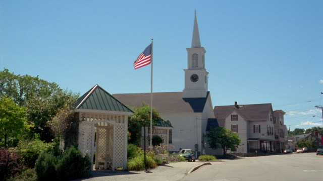 wide shot gazebo and us flag at bus stop in front of church with steeple / camden, maine - small town stock videos and b-roll footage