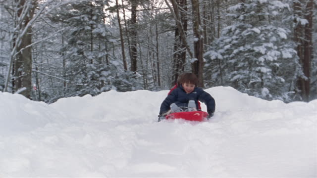 wide shot girl and boy sledding in snow / franconia, grafton county, new hampshire, usa - mitten stock videos and b-roll footage