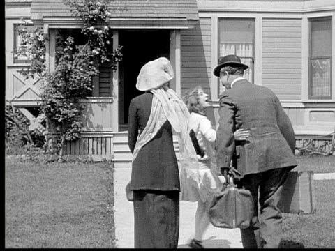 1913 B/W Wide shot Girl and parents walking together toward house and carrying luggage / USA