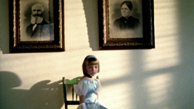 wide shot girl in fancy dress looking somber sitting on chair in front of framed portraits of 1800s people - gold dress stock videos & royalty-free footage