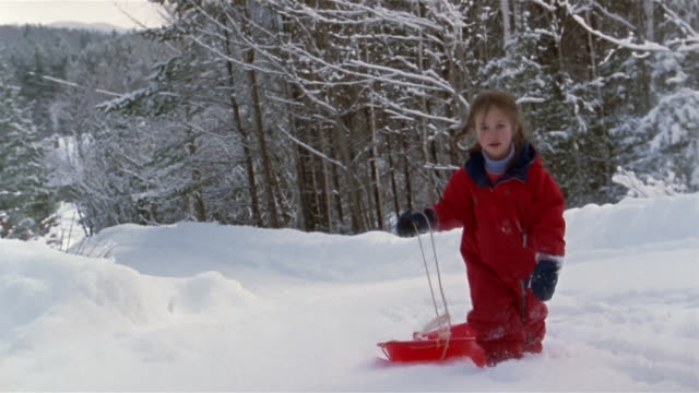 wide shot girl pulling sled and walking in snow / franconia, grafton county, new hampshire, usa - skijacke stock-videos und b-roll-filmmaterial