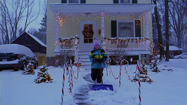 wide shot girl shoveling snow on front walk of house with christmas lights - decoration stock videos and b-roll footage