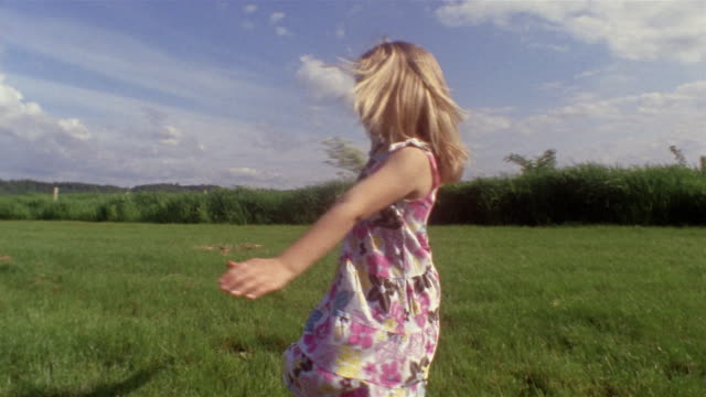 wide shot girl spinning in field and holding bunch of flowers / des moines, king county, washington, usa - dissolvenza in chiusura video stock e b–roll