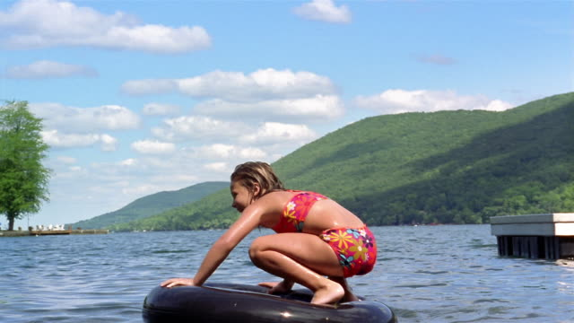 wide shot girl standing up on inner tube in lake / falling down / canandaigua lake, new york - inner tube stock videos and b-roll footage