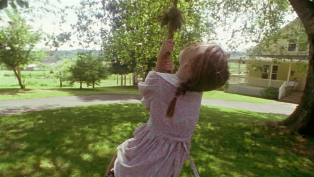 wide shot girl swinging on tire swing near house / des moines, king county, washington, usa - tyre swing stock videos & royalty-free footage