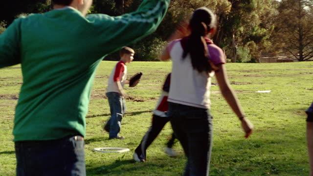 wide shot girl throwing ball / other kids waving base runners home - 野球用グローブ点の映像素材/bロール