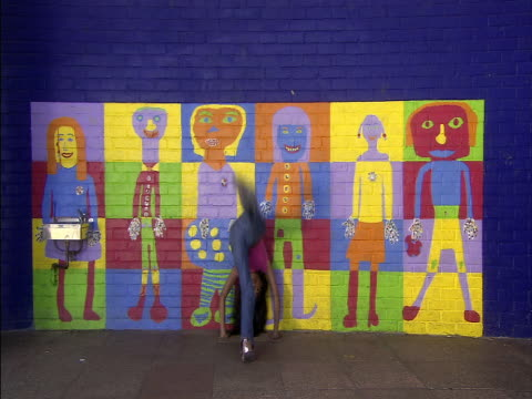 Wide shot girl walking in and doing handstand against brightly painted school wall/ London, England