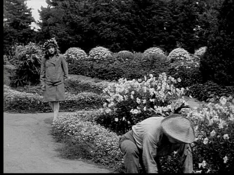 1913 b/w wide shot girl walking on path in garden and watching her grandfather working / usa  - 1913 stock-videos und b-roll-filmmaterial