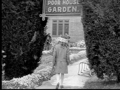 1913 b/w wide shot girl walking on path in garden outside poor house / usa  - garden path stock videos and b-roll footage