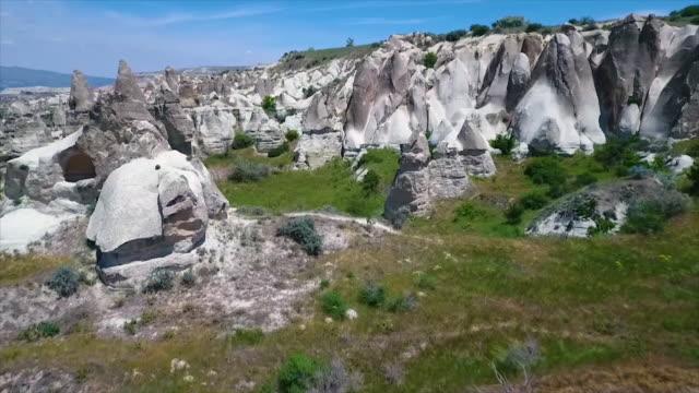 vídeos de stock e filmes b-roll de wide shot going over landscape and rocky hills - exposto ao ar