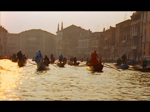wide shot gondoliers rowing gondolas on the water at sunset / pan rear view of person wearing carnivale costume riding in gondola - 17th century style stock videos & royalty-free footage
