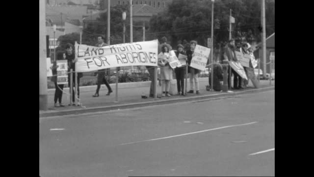 wide shot government building and traffic in front / white student protesters standing on the side side of spring street melbourne holding up signs... - 1968 bildbanksvideor och videomaterial från bakom kulisserna