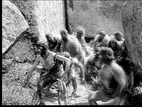 1914 b/w wide shot group of cavemen running past boulders through passageway - evolution stock-videos und b-roll-filmmaterial