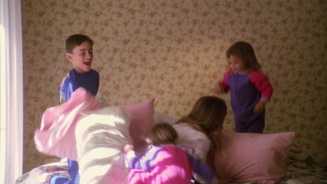 wide shot group of children having pillow fight on bed - 枕投げ点の映像素材/bロール