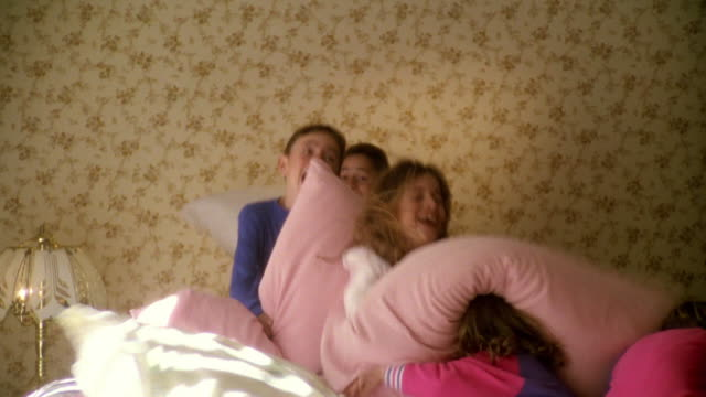 vídeos y material grabado en eventos de stock de wide shot group of children having pillow fight on bed - lucha con almohada