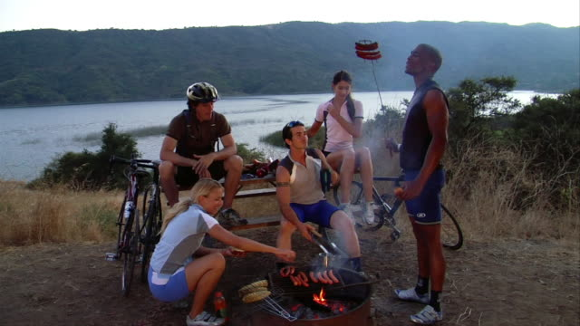 wide shot group of cyclists grilling hot dogs outdoors / lake in background - ワイドショット点の映像素材/bロール