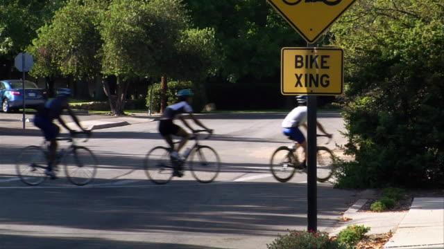 vídeos de stock, filmes e b-roll de wide shot group of cyclists riding in a line across road / passing behind a 'bike crossing' sign - menos de 10 segundos
