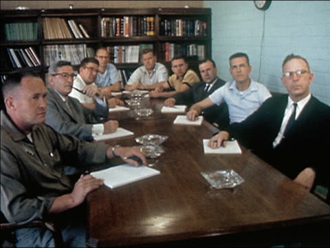 1962 wide shot group of men in conference room sitting around table and looking serious - 1962年点の映像素材/bロール