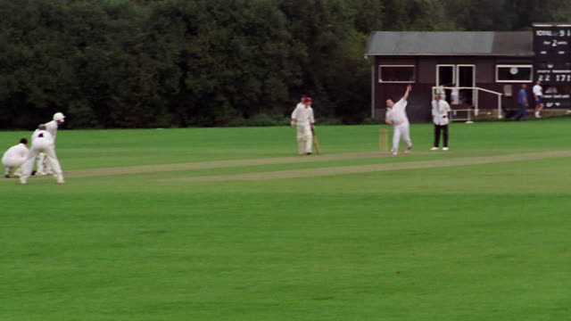 wide shot group of men in white uniforms play cricket on green lawn / trees in background / Hertfordshire, England