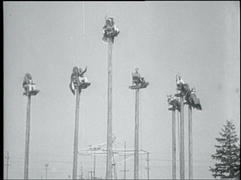 b/w 1931 wide shot group of men sitting on poles + waving at camera / seattle - 1931 stock videos & royalty-free footage