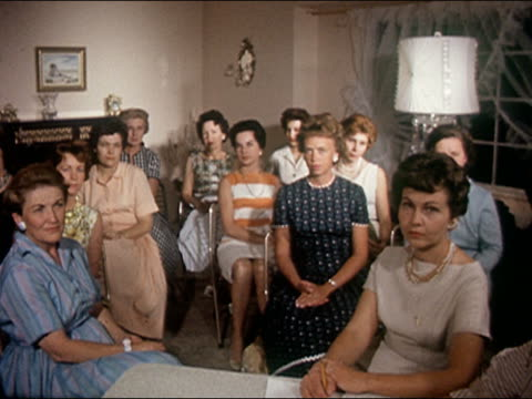 1962 wide shot group of middle aged suburban women in living room looking at camera / audio - starren stock-videos und b-roll-filmmaterial