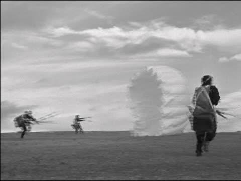 wide shot group of paratroopers landing / gathering parachutes / running away / one paratrooper dragged - 若い男性だけ点の映像素材/bロール