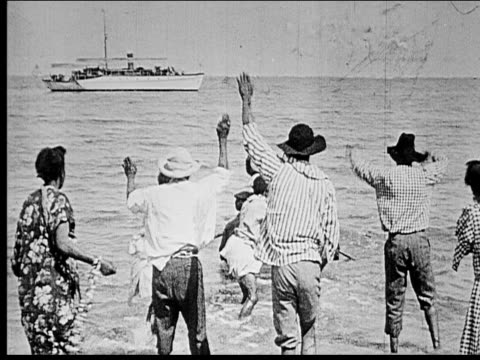 1914 b/w wide shot group of people waving goodbye to woman rowing out to steamship in sea - 1914 stock videos & royalty-free footage
