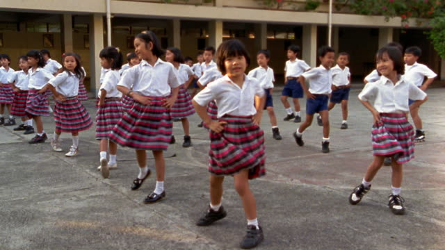 wide shot group of schoolchildren exercizing outdoors - indonesia stock videos & royalty-free footage