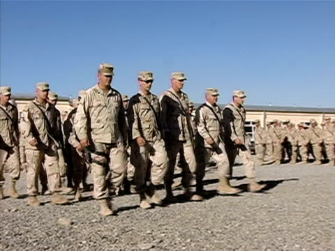 Wide shot group of soldiers marching up to general during awards ceremony/ Afghanistan