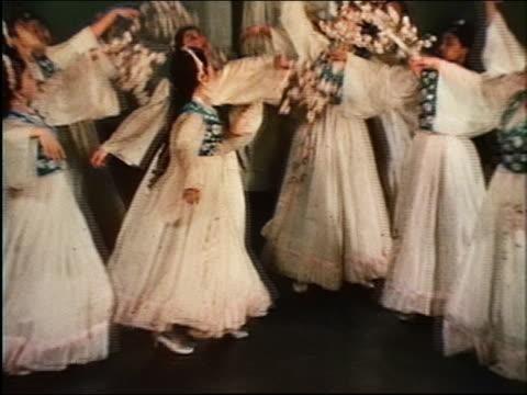 vídeos de stock e filmes b-roll de 1967 wide shot group of women in long dresses carrying flowers dancing in various formations / uzbekistan - sentar se